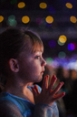 Close-up of thoughtful girl against defocused lights at night - CAVF38291