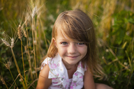 Portrait of happy girl sitting on farm - CAVF38297