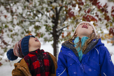 Playful siblings sticking out tongue while standing outdoors during winter - CAVF38324