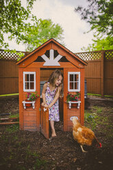 Happy girl looking at hen while standing on entrance of chicken coop - CAVF38327