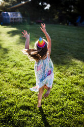 Cheerful girl in party hat jumping on grassy field at backyard - CAVF38336
