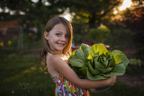 Happy girl carrying lettuce in bowl at backyard - CAVF38342