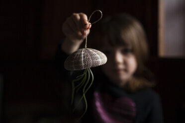 Girl playing with air plant hanging from sea urchin at home - CAVF38375