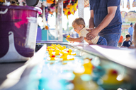 Father lifting son playing with rubber ducks floating in water at amusement park - CAVF38381