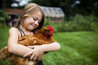 Smiling girl holding hen while standing in yard - CAVF38393
