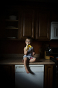 Portrait of boy eating banana while sitting on kitchen counter at home - CAVF38417