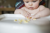 Close-up of baby girl playing with banana on high chair at home - CAVF38444