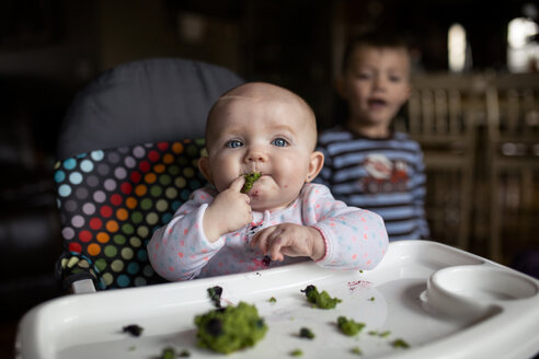 Baby girl eating food on high chair while brother standing in background - CAVF38462