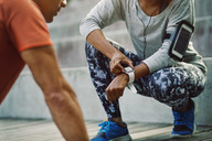 Woman using smart watch while friend doing push-ups on steps - MASF03782