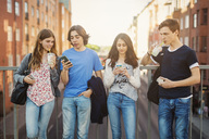 Teenagers using smart phone while drinking juice on bridge in city - MASF03791