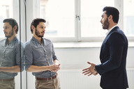 Young businessman discussing with male colleague in office - MASF03797