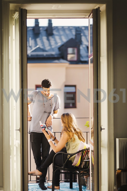 Young couple reading guidebook while planning vacations at balcony - MASF03827