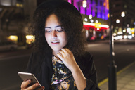 Woman using smart phone sidewalk in city at night - MASF03854