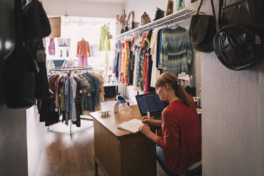 Woman working at desk while sitting in thrift store - MASF03857