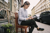 Woman reading paper while sitting on chair against store in city - MASF03860