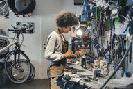 Side view of female mechanic working in bicycle workshop - MASF03866