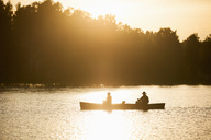 Silhouette father and son traveling in canoe on lake during sunset - MASF03872