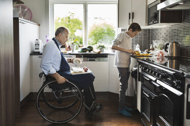 Son with disabled father cutting vegetables in kitchen - MASF03875