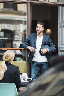 Smiling businessman holding helmet while talking to colleague at sidewalk cafe - MASF03878