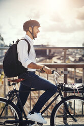 Smiling businessman with bicycle looking at city view while standing on bridge - MASF03881