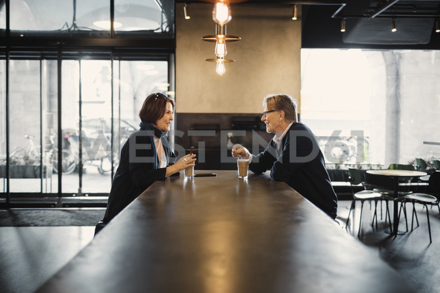 Side view of senior couple talking while having coffee at cafeteria - MASF03884
