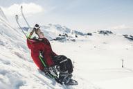 Side view of girl in ski-wear relaxing on ski slope - MASF03890