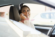 Smiling businesswoman looking away while using smart phone in car - MASF03896