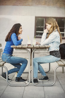 Side view of female teenagers talking at table outdoors - MASF03899