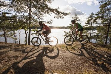 Side view of man and woman cycling at lakeshore - MASF03914