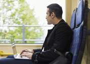 Side view of young man using laptop while looking through tram window - MASF03920