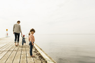 Side view of girl looking at sea while standing on pier with family walking in background against sky - MASF03926