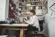 Side view of industrial designer analyzing product at home office - MASF03944