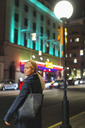 Side view of woman standing on sidewalk in city during night - MASF03947