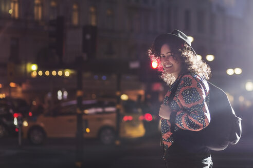 Side view portrait of smiling woman standing on city street at night - MASF03950