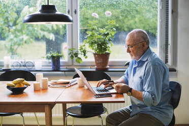 Side view of senior man using credit card for online shopping at home - MASF03956