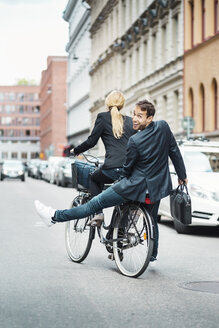Rear view portrait of happy businessman sitting on back seat while female colleague riding bicycle - MASF03962