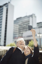 Senior couple taking selfie through smart phone in city - MASF03977