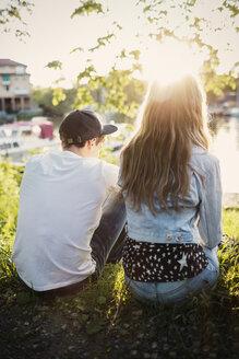 Rear view of teenage couple sitting at lakeshore - MASF03989