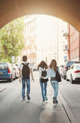 Rear view of teenagers walking in tunnel - MASF03995