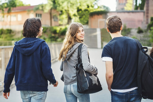 Rear view portrait of smiling female teenager walking with male friends on bridge - MASF03998