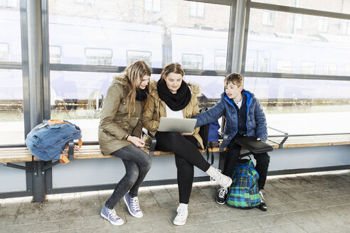 School students using laptop on bench at train station - MASF04004