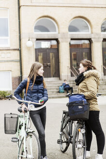 Schoolgirls with bicycles talking outside school building - MASF04007