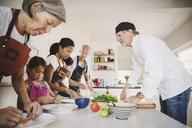 Senior man guiding family in preparing Asian food at kitchen - MASF04010