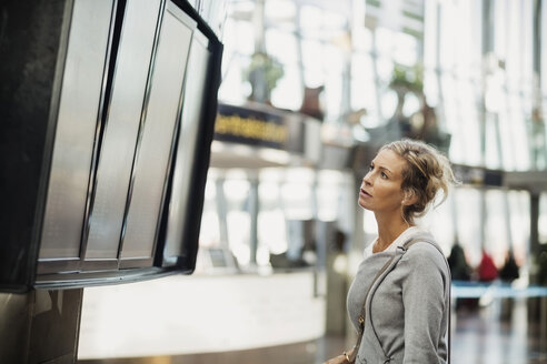 Side view of businesswoman reading arrival departure board at airport - MASF04016