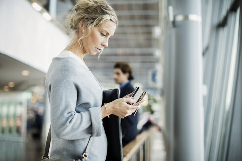 Side view of businesswoman using smart phone at airport - MASF04019