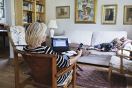 Senior woman using smart phone at home while dog relaxing on sofa - MASF04025