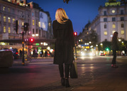 Rear view of woman walking on city street at night - MASF04031