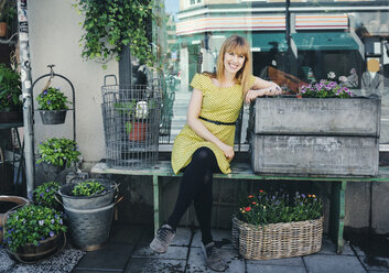 Portrait of happy owner leaning on crate outside plant shop - MASF04043