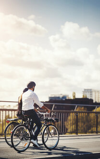 Rear view of business people riding bicycles on bridge against sky - MASF04049