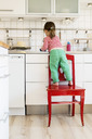 Rear view of girl standing on chair while working in kitchen - MASF04052